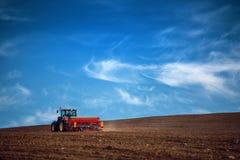 Agricoltore con il trattore che semina i raccolti al campo Immagine Stock