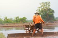 Agricoltore con il trattore condotto a piedi nella stagione d'agricoltura in anticipo Immagine Stock