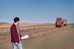 Agricoltore con il trattore sul campo Immagini Stock Libere da Diritti