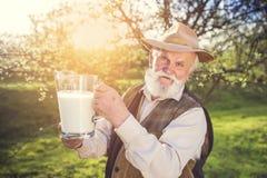 Agricoltore con la brocca di latte Immagini Stock Libere da Diritti