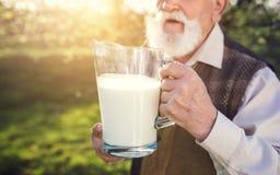 Agricoltore con la brocca di latte Fotografia Stock