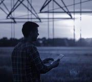 Agricoltore con la compressa davanti all'impianto di irrigazione Immagini Stock Libere da Diritti