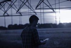 Agricoltore con la compressa davanti all'impianto di irrigazione Fotografia Stock Libera da Diritti