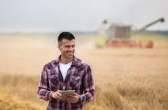 Agricoltore con la compressa nel campo durante il raccolto fotografia stock libera da diritti