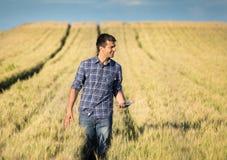 Agricoltore con la compressa nel giacimento di grano Fotografia Stock