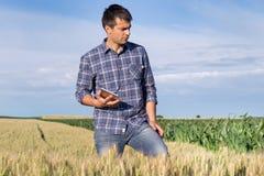 Agricoltore con la compressa nel giacimento di grano Fotografia Stock Libera da Diritti