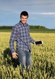 Agricoltore con la compressa nel giacimento di grano verde Fotografie Stock Libere da Diritti