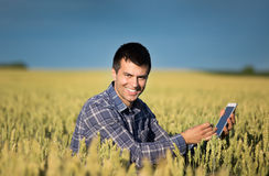 Agricoltore con la compressa nel giacimento di grano verde Fotografie Stock