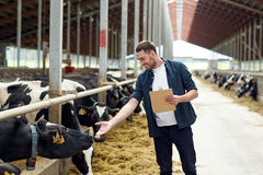 Agricoltore con la lavagna per appunti e le mucche in stalla sull'azienda agricola Immagini Stock Libere da Diritti
