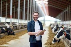 Agricoltore con la lavagna per appunti e le mucche in stalla sull'azienda agricola Fotografie Stock Libere da Diritti