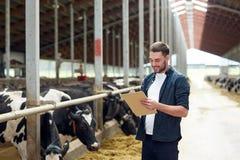 Agricoltore con la lavagna per appunti e le mucche in stalla sull'azienda agricola Fotografia Stock