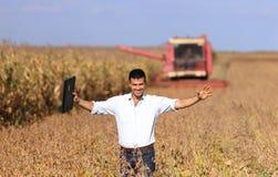 Agricoltore con la mietitrebbiatrice nel giacimento della soia Fotografie Stock Libere da Diritti