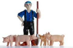 Agricoltore con la plastica del giocattolo dei maiali Fotografie Stock