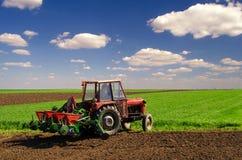 Agricoltore con la semina del trattore sui campi agricoli in primavera Fotografia Stock