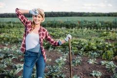 Agricoltore con la zappa che funziona nel campo Fotografie Stock Libere da Diritti