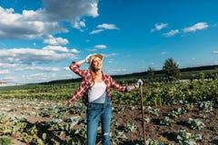 Agricoltore con la zappa che funziona nel campo Immagini Stock