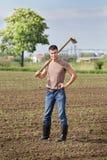 Agricoltore con la zappa nel campo di grano Immagini Stock