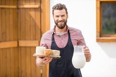 Agricoltore con latte e formaggio all'aperto Fotografia Stock Libera da Diritti