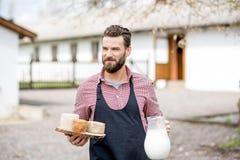 Agricoltore con latte e formaggio all'aperto Fotografia Stock