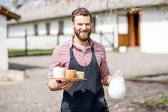 Agricoltore con latte e formaggio all'aperto Fotografie Stock
