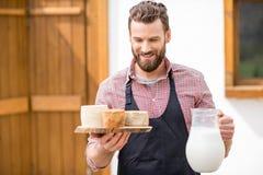 Agricoltore con latte e formaggio all'aperto Fotografie Stock Libere da Diritti