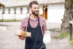 Agricoltore con latte e formaggio all'aperto Immagini Stock