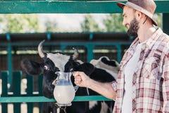 Agricoltore con latte fresco nella stalla Fotografia Stock Libera da Diritti