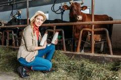 Agricoltore con latte fresco nella stalla Fotografia Stock
