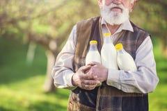 Agricoltore con le bottiglie per il latte Immagini Stock