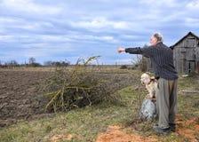 Agricoltore con un cane che sta sul campo Immagine Stock Libera da Diritti