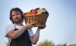 Agricoltore con un raccolto ecologico delle verdure in un canestro vicino Fotografia Stock