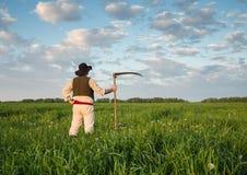 Agricoltore con una falce sul campo verde Immagini Stock Libere da Diritti