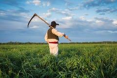 Agricoltore con una falce sul campo verde Immagine Stock