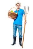 Agricoltore con una forca e un canestro delle verdure Fotografia Stock