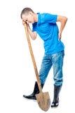 Agricoltore con una pala che tiene il suo mano una parte posteriore irritata su un bianco Fotografia Stock