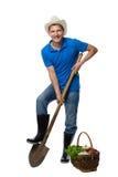 Agricoltore con una pala e le verdure del raccolto immagine stock