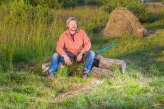 Agricoltore con una seduta dell'ascia Fotografie Stock Libere da Diritti