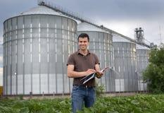 Agricoltore davanti al silo di grano Fotografia Stock
