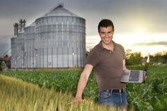 Agricoltore davanti al silo di grano Fotografie Stock Libere da Diritti