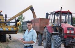 Agricoltore davanti al trattore ed alla mietitrebbiatrice durante il raccolto Immagine Stock Libera da Diritti