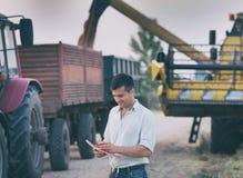 Agricoltore davanti al trattore ed alla mietitrebbiatrice durante il raccolto Fotografie Stock Libere da Diritti