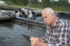 Agricoltore del pesce che controlla compressa al lavoratore Fotografia Stock Libera da Diritti