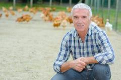 Agricoltore del pollame nel campo Immagine Stock