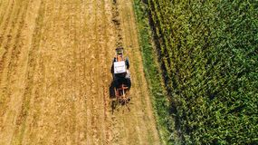 Agricoltore della mietitrice che per mezzo del trattore con i rastrelli rotatori per la raccolta del fieno Vista aerea del fuco,  Immagine Stock Libera da Diritti