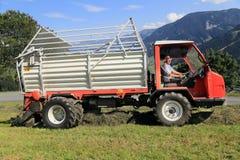 Agricoltore della montagna sulla mietitrice del fieno Fotografia Stock