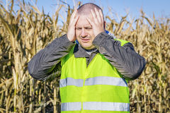Agricoltore depresso ad all'aperto sul campo di grano freddo Immagine Stock