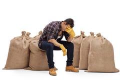 Agricoltore depresso che si siede su un sacco della tela da imballaggio Fotografia Stock