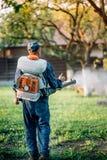 Agricoltore di agricoltura che spruzza gli antiparassitari organici sul giardino di frutticoltura Fotografia Stock Libera da Diritti