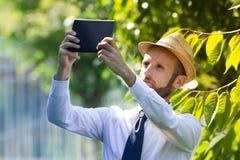 Agricoltore di Digital che controlla il suo campo Immagine Stock