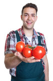 Agricoltore di risata che offre i pomodori freschi Immagini Stock Libere da Diritti